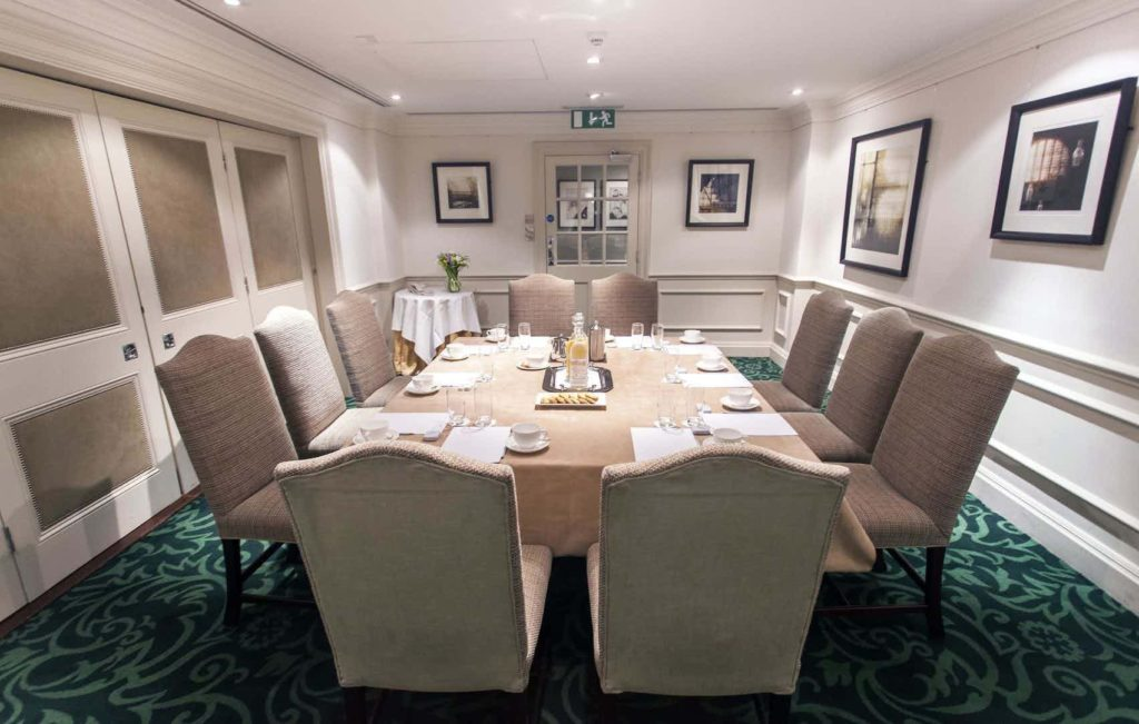 private room with rectangular table and chairs with framed photographs on the walls