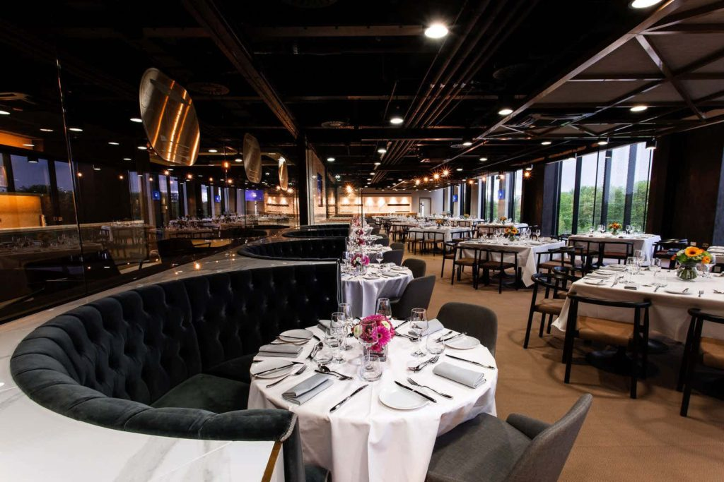 private dining area with round tables and boothed seats