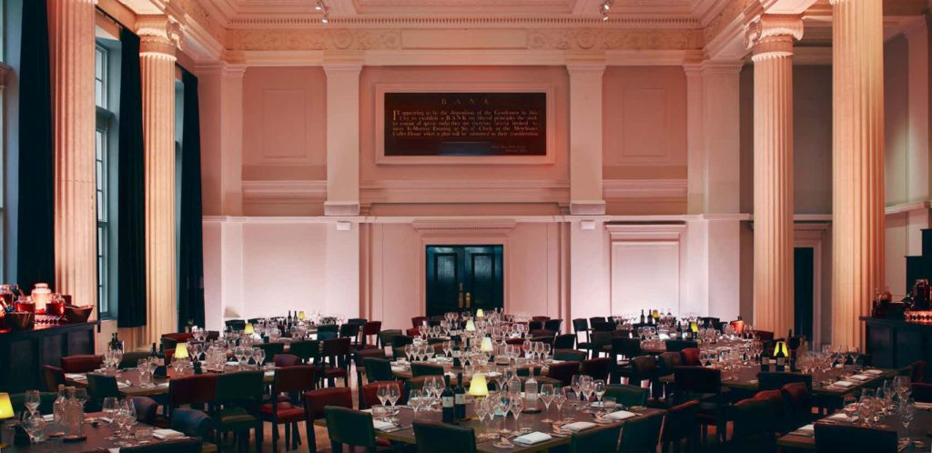 large hall wit square tables and chairs with large pillars either side of the room