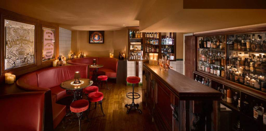 private room with bar and red stools and red booths