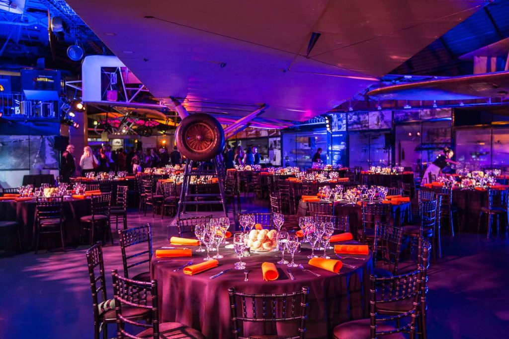 event space with aviation models hanging from the ceiling, blue lighting and round tables